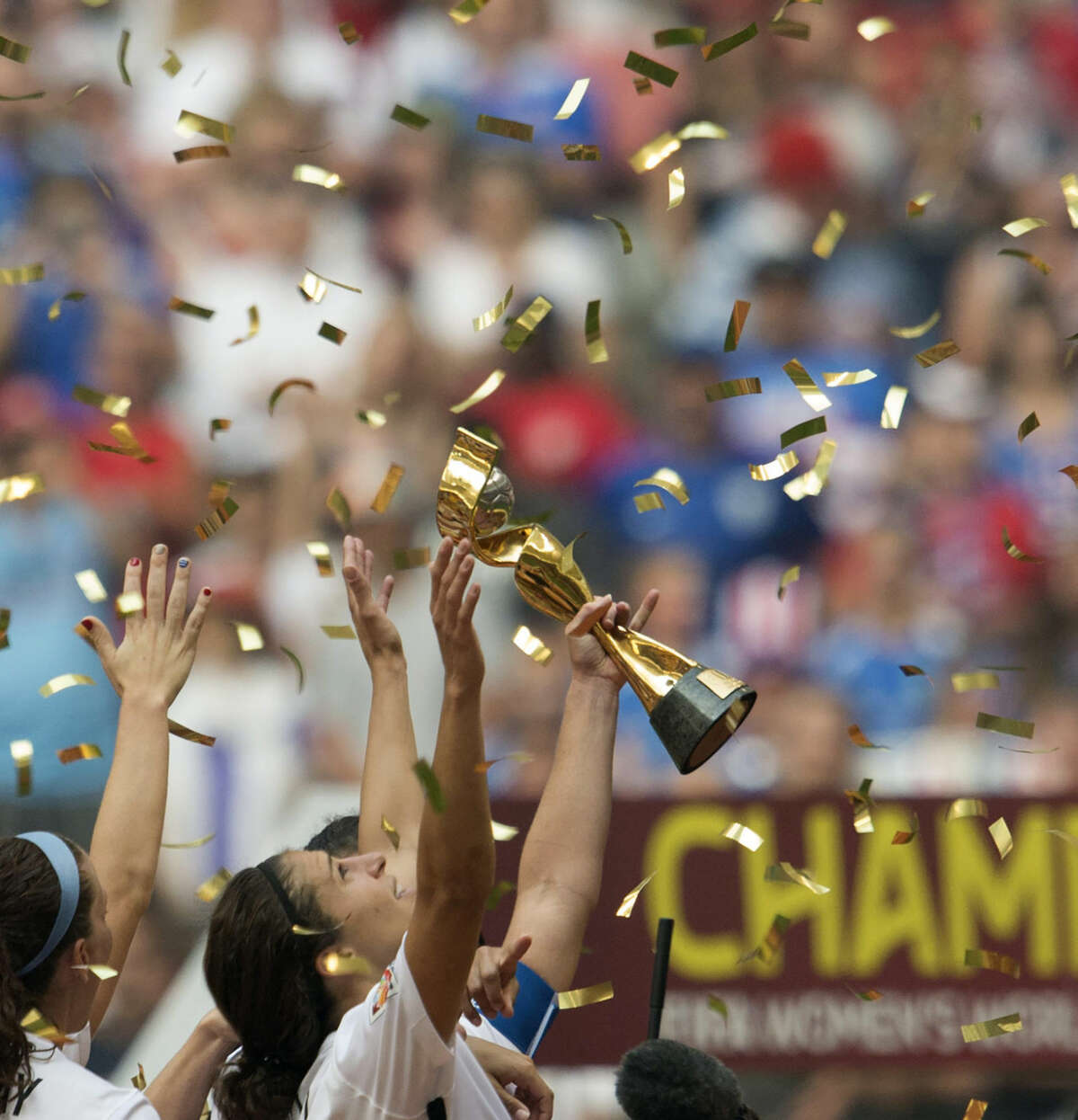 USA team members lift the trophy in celebration following their win over Japan at the FIFA Women's World Cup soccer championship in Vancouver, British Columbia, Canada, Sunday, July 5, 2015. (Jonathan Hayward/The Canadian Press via AP) MANDATORY CREDIT