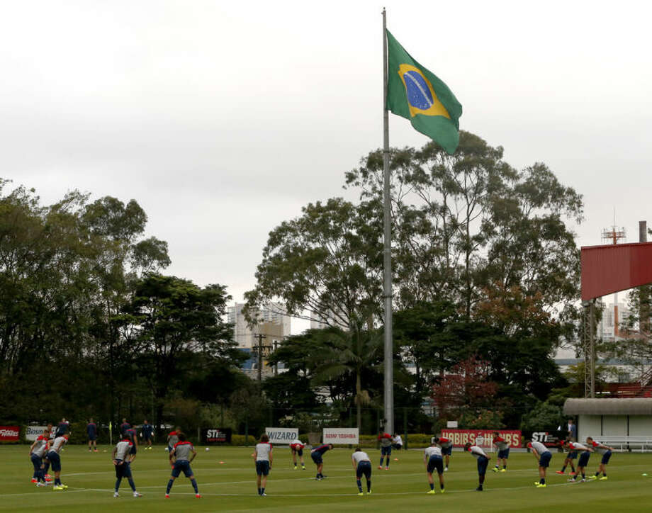United States players stretch at the beginning of a training session as a Brazilian flags flies in the background, at the Sao Paulo FC training center in Sao Paulo, Brazil, Monday, June 9, 2014. The U.S. will play in group G of the 2014 soccer World Cup. (AP Photo/Julio Cortez)