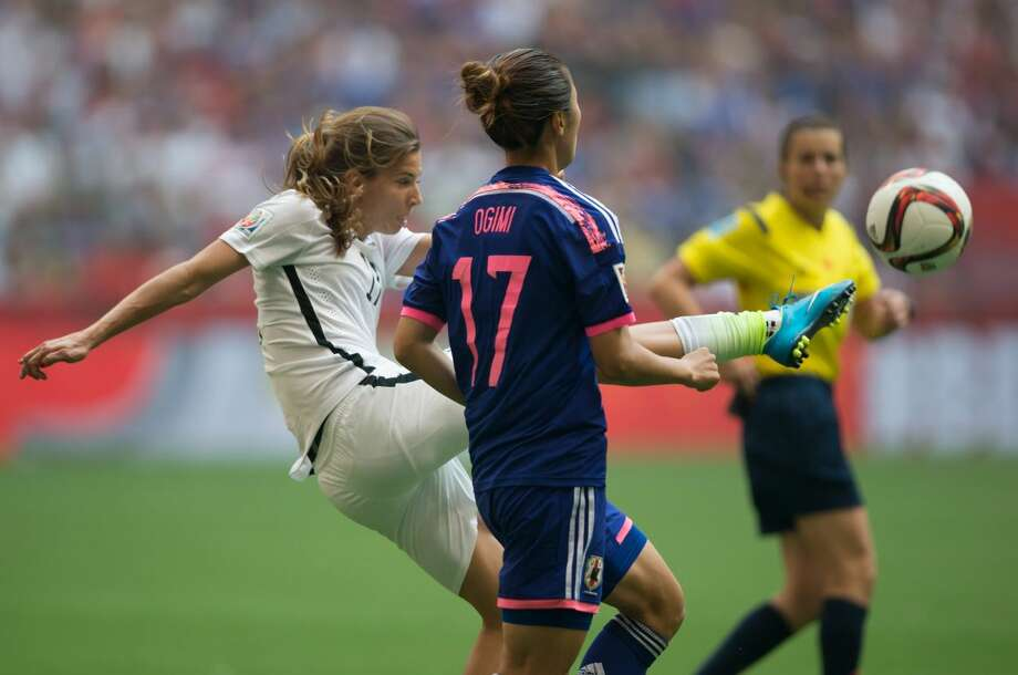 United States' Tobin Heath, left, kicks the ball away from Japan's Yuki Ogimi during the second half of the FIFA Women's World Cup soccer championship in Vancouver, British Columbia, Canada, on Sunday, July 5, 2015. (Darryl Dyck/The Canadian Press via AP) MANDATORY CREDIT