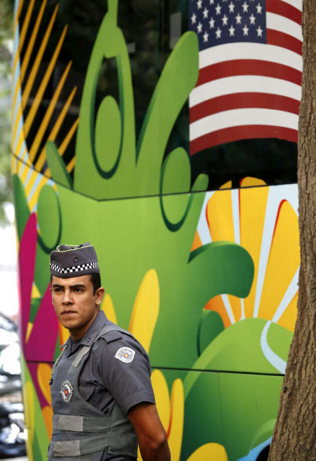 A police officer stands guard as the bus transporting members of the United States national soccer team, arrives at the team hotel in Sao Paulo, Brazil, Monday, June 9, 2014. The U.S. will play in group G of the 2014 soccer World Cup. (AP Photo/Julio Cortez)