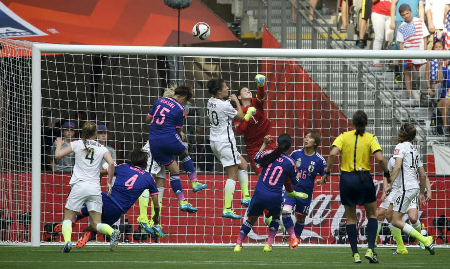 United States goalkeeper Hope Solo (1), center, punches away a shot from Japan during the second half of the FIFA Women's World Cup soccer championship in Vancouver, British Columbia, Canada, Sunday, July 5, 2015. (AP Photo/Elaine Thompson)