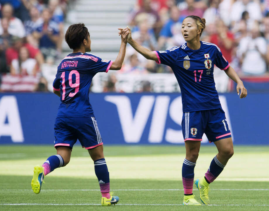 Japan's Yuki Ogimi, right, and Saori Ariyoshi celebrate Ogimi's goal against the United States during first half action in the FIFA Women's World Cup soccer soccer championship in Vancouver, British Columbia, Canada, Sunday, July 5, 2015. (Jonathan Hayward/The Canadian Press via AP) MANDATORY CREDIT