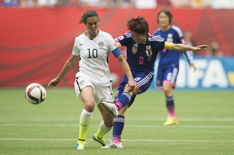 Japan's Aya Miyama, right, is challenged by United States' Carli Lloyd during the first half of the FIFA Women's World Cup soccer championship in Vancouver, British Columbia, Canada, Sunday, July 5, 2015. (Jonathan Hayward/The Canadian Press via AP) MANDATORY CREDIT