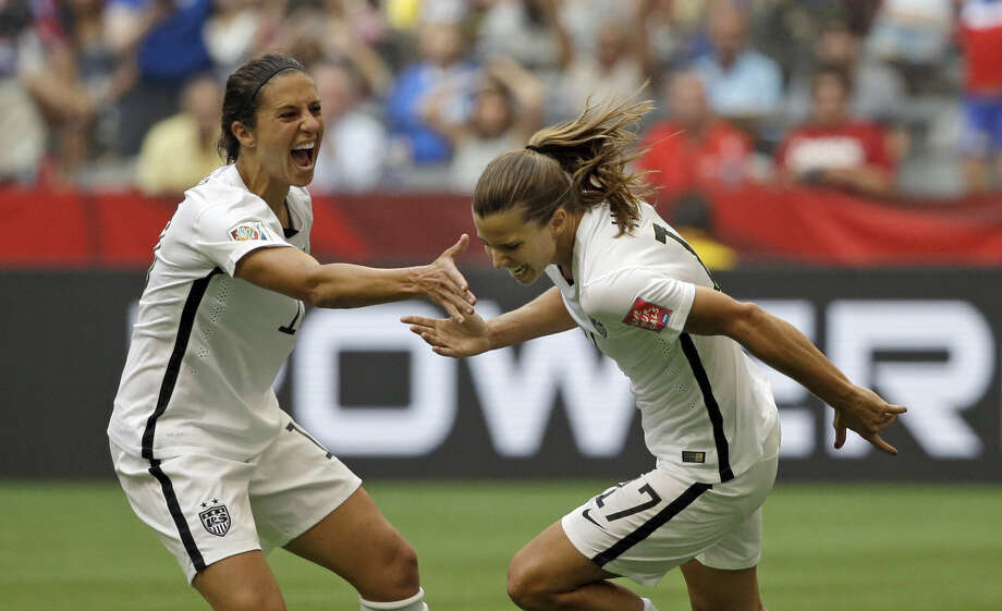 United States' Tobin Heath, right, celebrates with Carli Lloyd, left, after Heath scored a goal against Japan during the second half of the FIFA Women's World Cup soccer championship in Vancouver, British Columbia, Canada, Sunday, July 5, 2015. (AP Photo/Elaine Thompson)