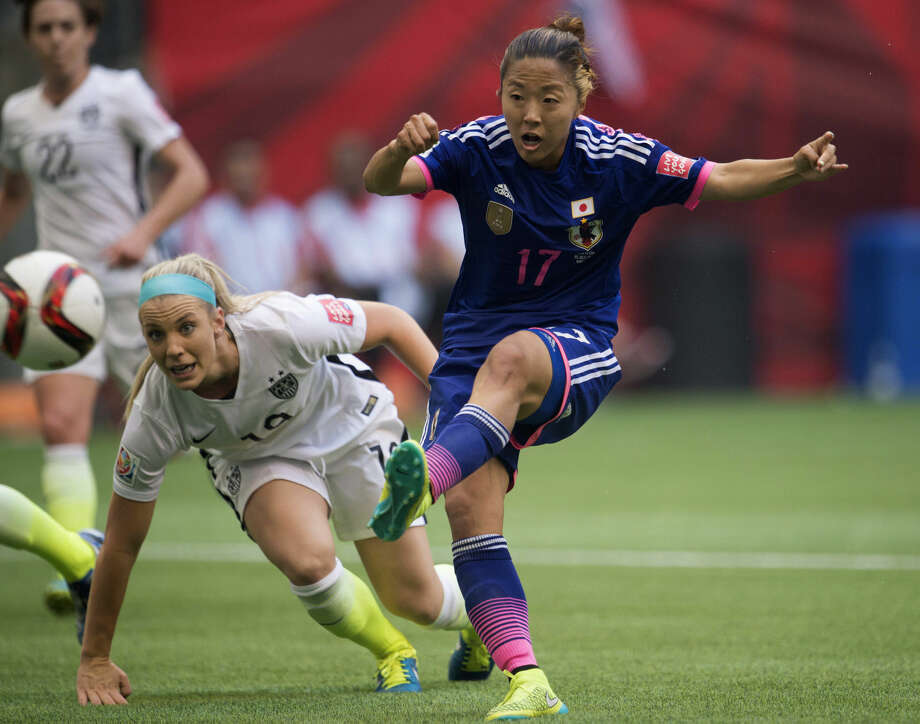 Japan's Yuki Ogimi, right, scores a goal as United States' Julie Johnston watches during the first half of the final of the FIFA World Cup soccer championship in Vancouver, British Columbia, Canada, Sunday, July 5, 2015. (Jonathtan Hayward/The Canadian Press via AP) MANDATORY CREDIT