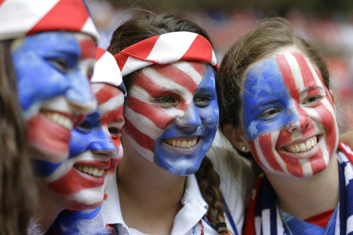 United States fans with painted faces smile in the stands before the start of the FIFA Women's World Cup soccer championship between the U.S. and Japan in Vancouver, British Columbia, Canada, Sunday, July 5, 2015. (AP Photo/Elaine Thompson)