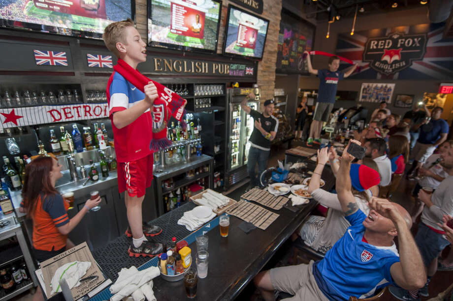 MacKale Crimmins, 11, stands on the bar while watching the FIFA Women's World Cup soccer championship between the United States and Japan, Sunday, July 5, 2015, from Royal Oak, Mich. (David Guralnick/Detroit News via AP) DETROIT FREE PRESS OUT; HUFFINGTON POST OUT; MANDATORY CREDIT