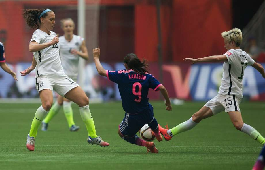 Japan's Nahomi Kawasumi (9) tries to stop a pass from United States' Megan Rapinoe, right, to Lauren Holiday during first half FIFA Women's World Cup soccer championship in Vancouver, British Columbia, Canada, Sunday, July 5, 2015. (Darryl Dyck/The Canadian Press via AP) MANDATORY CREDIT