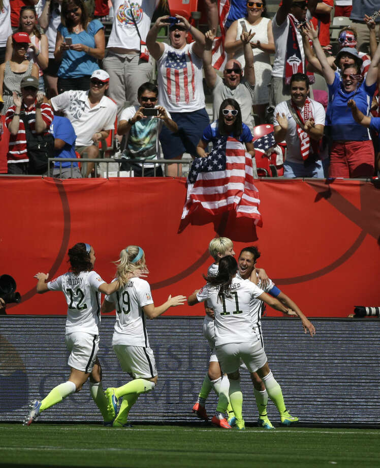 From left, United States' Carli Lloyd, right, celebrates with teammates after Lloyd scored a goal against Japan during the first half of the FIFA Women's World Cup soccer championship in Vancouver, British Columbia, Canada, Sunday, July 5, 2015. (AP Photo/Elaine Thompson)