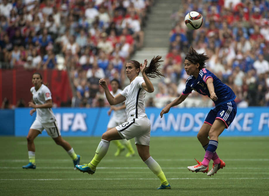 Japan's Saki Kumagai heads the ball away as US player Alex Morgan watches on during second half action at the FIFA Women's World Cup isoccer championship in Vancouver, British Columbia, Canada, Sunday, July 5, 2015. (Jonathan Hayward/The Canadian Press via AP) MANDATORY CREDIT