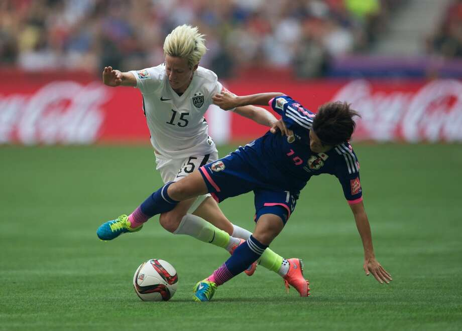 United States' Megan Rapinoe, left, and Japan's Homare Sawa fight for the ball during first half FIFA Women's World Cup soccer championship in Vancouver, British Columbia, Canada, Sunday, July 5, 2015. (Darryl Dyck/The Canadian Press via AP) MANDATORY CREDIT