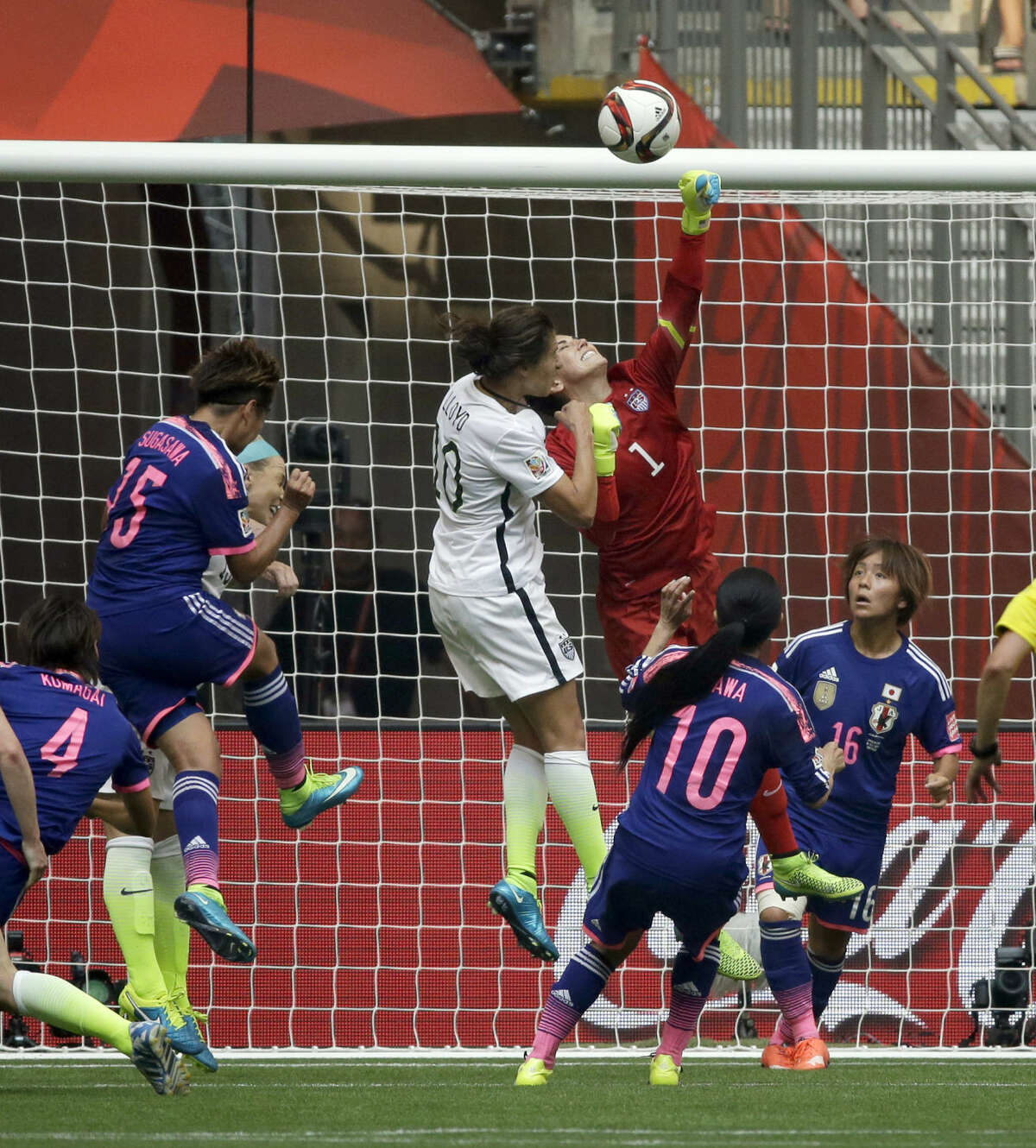 United States goalkeeper Hope Solo (1), center, punches away a shot as Japan's Mana Iwabuchi (16) and Homare Sawa (10) look on during the second half of the FIFA Women's World Cup soccer championship in Vancouver, British Columbia, Canada, Sunday, July 5, 2015. (AP Photo/Elaine Thompson)