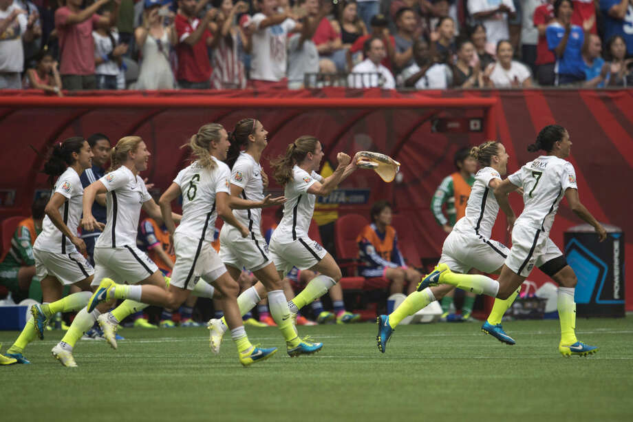 United States' players rush on to the field after the FIFA Women's World Cup soccer championship final against Japan in Vancouver, British Columbia, Canada, Sunday, July 5, 2015. The United States won 5-2. (Jonathtan Hayward/The Canadian Press via AP) MANDATORY CREDIT