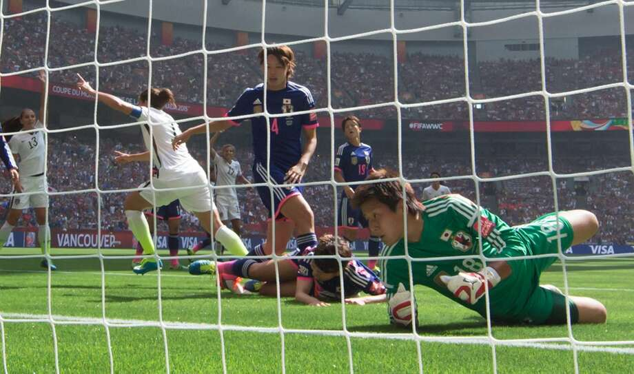 Japan goalkeeper Ayumi Kaihori, (18) right, and Saki Kumagai (4) look into the net as United States' Carli Lloyd, second from left, celebrates her second goal during the first half of the FIFA Women's World Cup soccer championship in Vancouver, British Columbia, Canada, on Sunday, July 5, 2015. (Darryl Dyck/The Canadian Press via AP) MANDATORY CREDIT
