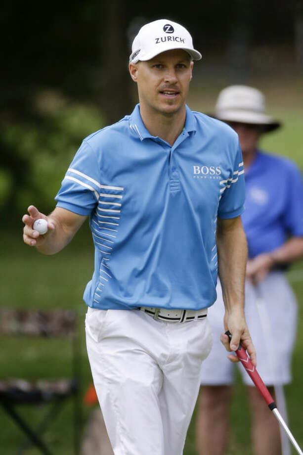 Ben Crane acknowledges the crowd after making his par putt on the 17th green during the third round of the St. Jude Classic golf tournament, Sunday, June 8, 2014, in Memphis, Tenn. Weather delays during the week forced Saturday's third round to be finished Sunday morning before the final round could begin. (AP Photo/Mark Humphrey)