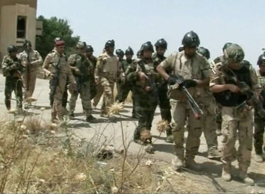 In this Monday, June 9, 2014 image taken from video obtained from the Iraqi Military, which has been authenticated based on its contents and other AP reporting, military soldiers prepare to take their positions during clashes with militants in the northern city of Mosul, Iraq. Insurgents on Tuesday pressed their efforts to seize effective control of Iraq's second-largest city of Mosul on Tuesday after Iraqi security forces abandoned their posts and militants overran the provincial government headquarters and other key buildings, dealing a serious blow to Baghdad's attempts to tame a widening insurgency in the country. (AP Photo/Iraqi Military via AP video)