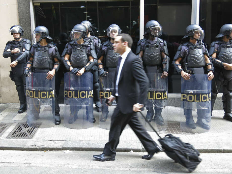A pedestrian walks by a line of police officers as they block the entrance of the Transportation Department when subway workers arrive to request a meeting with officials, to negotiate better salaries and benefits in Sao Paulo, Brazil, Monday, June 9, 2014. Striking subway workers clashed in a central commuter station Monday while union leaders threatened to maintain the work stoppage through the World Cup's opening match in Sao Paulo this week. (AP Photo/Adriana Gomez Licon)