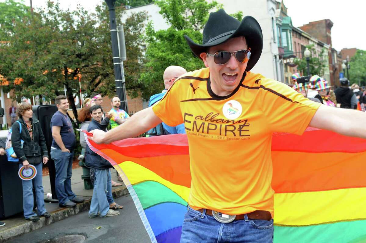 Dan Bollana with Albany Empire LGBT Soccer Club, right, uses his flag as a cape in the Capital PRIDE Parade on Saturday, June 11, 2016, in Albany, N.Y. The annual parade, festival and rally celebrates the Lesbian, Gay, Bisexual, Transgender and Queer community with entertainment and family-friendly activities. (Cindy Schultz / Times Union)