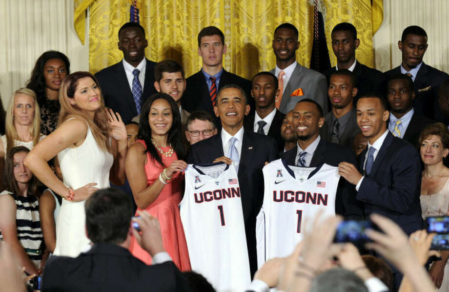 President Barack Obama poses for a photo with the NCAA Champion UConn Huskies Men's and Women's Basketball teams in the East Room of the White House in Washington, Monday, June 9, 2014. Obama welcomed the two team to the White House to honor their 2014 NCAA Championships. Standing in the front row with Obama are, from left, women's basketball players Stefanie Dolson and Bria Hartley, and men's players Ryan Boatright and Shabazz Napier. (AP Photo/Susan Walsh)