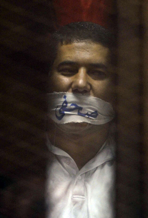 """FILE - In this May 16, 2015 file photo, Egyptian journalist Ibrahim el Darawy wears a cloth over his mouth with Arabic that reads, """"journalists"""" in the defendants cage of a makeshift courtroom at the national police academy, in eastern Cairo, Egypt. The government is pushing through a controversial new anti-terrorism draft bill that would set up special terrorism courts, shorten the appeals process, give police greater powers of arrest and imprison journalists who report information on attacks that differs from the official government line, a judicial official said Monday, July 6. (AP Photo/Ahmed Omar, File)"""