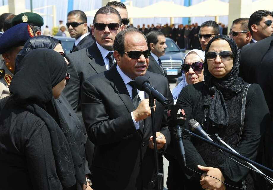 FILE - In this Tuesday, June 30, 2015 file photo, provided by the office of the Egyptian Presidency, President Abdel-Fattah el-Sissi, center, speaks at the funeral of the top public prosecutor Hisham Barakat, killed in a terrorist attack, as he was surrounded by Barakat's family members in Cairo, Egypt. After a series of stunning militant attacks, including the assassination of Barakat, the government is pushing through a new controversial anti-terrorism draft bill. (Egyptian Presidency via AP, File)