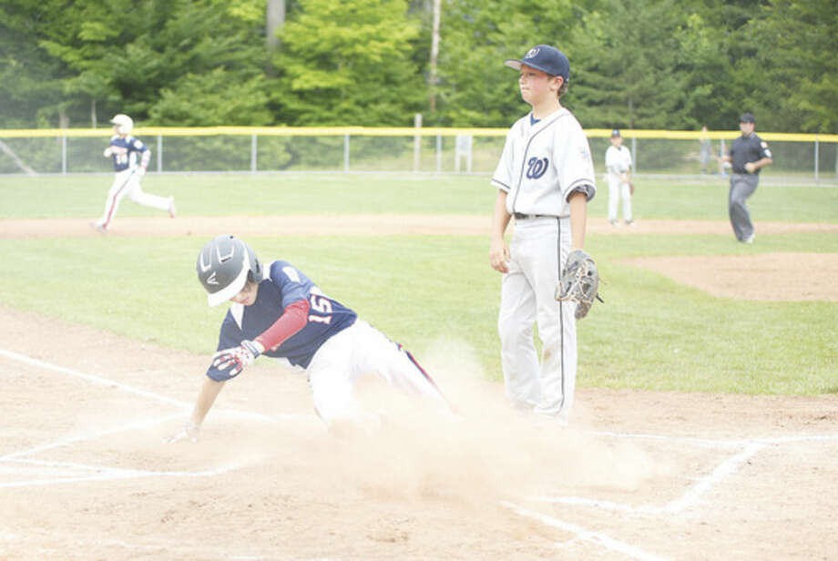 Hour photo/Danielle CallowayNorwalk's Alistair Morin, slides into home safely against Wilton on Monday.