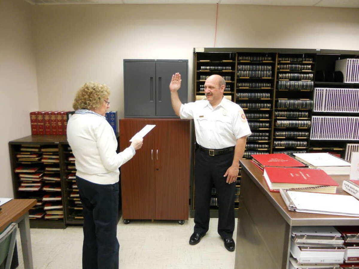 Wilton Town Clerk Betty Ragognetti swearing in Wilton Fire Chief Ronald Kanterman on Thursday, June 4.