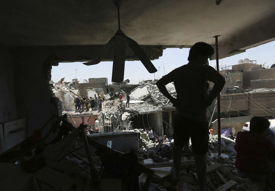 People stand in rubble after a bombing attack in the eastern neighborhood of New Baghdad. Iraq, Monday, July 6, 2015. At least a dozen civilians were killed on Monday when a Russian-made fighter jet accidentally dropped a bomb over a Baghdad neighborhood, officials said. (AP Photo/ Hadi Mizban)