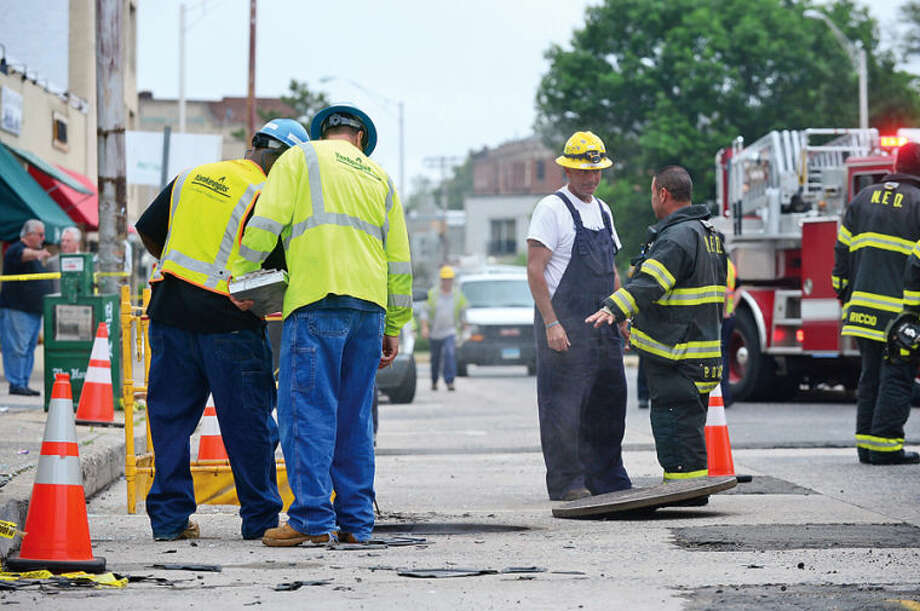Hour photo / Erik Trautmann CL&P and Norwalk firefighters investigate an underground explosion that rocked that Main St Tuesday morning blowing out windows at Muro's New York Bakery and knocking out power to the area.