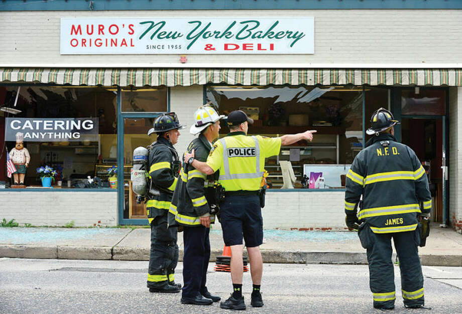 Hour photo / Erik Trautmann The Norwalk Police and Fire Departments investigate an underground explosion that rocked Main St Tuesday morning blowing out windows at Muro's New York Bakery and knocking out power to the area.