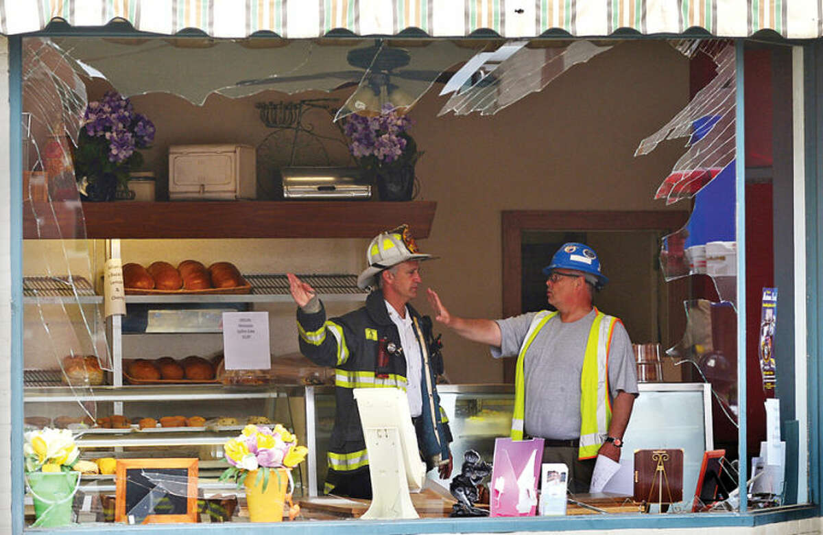 Hour photo / Erik Trautmann The Norwalk Fire Department and Yankee Gas investigate an underground explosion that rocked Main St Tuesday morning blowing out windows at Muro's New York Bakery and knocking out power to the area.