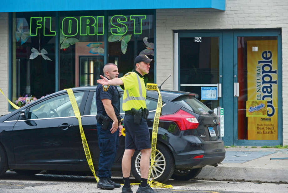 Hour photo / Erik Trautmann Norwalk police respond to an underground explosion that rocked Main St Tuesday morning knocking out windows Muro's New York Bakery and blowing a manhole cover into the undercarriage of a BMW.