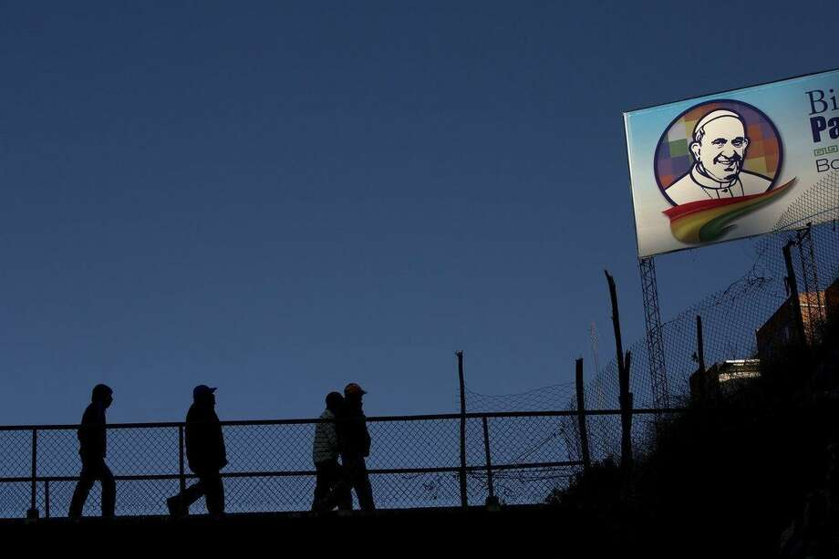 People walk near a sign with the image of Pope Francis in El Alto, Bolivia, Tuesday, July 7, 2015. Due to the altitude, Pope Francis will spend only a few hours in the capital city La Paz, which is near El Alto, during his South American tour. The pope arrives to Bolivia on Wednesday. (AP Photo/Rodrigo Abd)