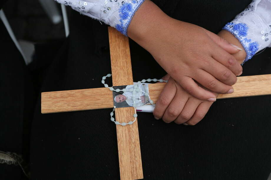 A woman holds a rosary and a wooden cross with an image of Pope Francis as she waits for the arrival of the Pontiff in San Francisco square, Quito, Ecuador, Tuesday, July 7, 2015. Francis is scheduled to meet with members of Ecuador's civil society and give and address in San Francisco Church. (AP Photo/Fernando Llano)