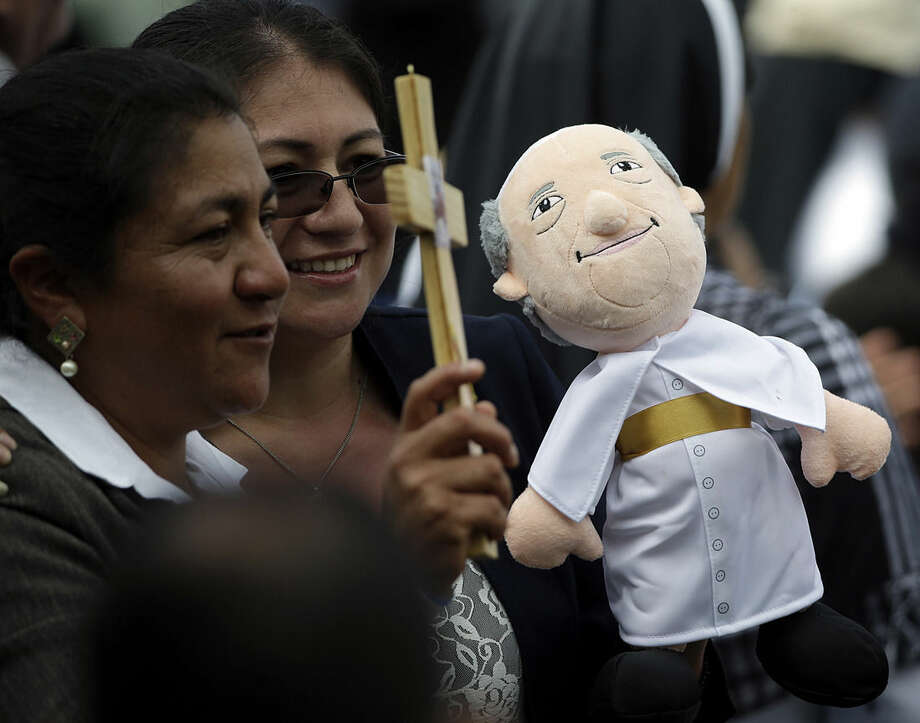 Faithful hold a cross and a doll of Pope Francis as they wait for the Pontiff's arrival to the Catholic University in Quito, Ecuador, Tuesday, July 7, 2015. On his final full day in Quito Pope Francis pressed his case for a new economic and environmental world order saying the goods of the Earth are meant for everyone and must not be exploited by the wealthy few for short-term profit at the expense of the poor. (AP Photo/Gregorio Borgia)