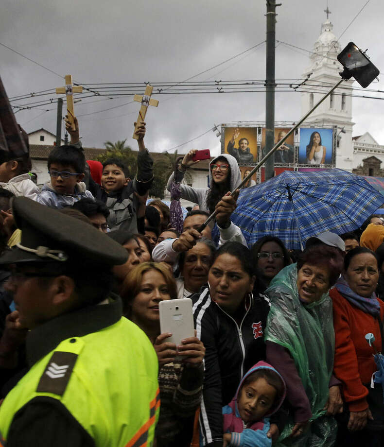 Faithful wait for the arrival of Pope Francis to the San Francisco Church in Quito, Ecuador, Tuesday, July 7, 2015. On his final full day in Quito Pope Francis pressed his case for a new economic and environmental world order saying the goods of the Earth are meant for everyone and must not be exploited by the wealthy few for short-term profit at the expense of the poor. (AP Photo/Gregorio Borgia)