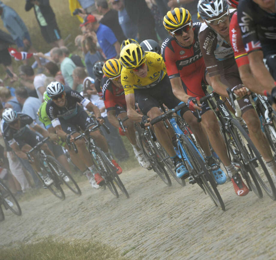 Britain's Christopher Froome, wearing the overall leader's yellow jersey, rides in the pack as it passes over a cobblestone sector during the fourth stage of the Tour de France cycling race over 223.5 kilometers (138.9 miles) with start in Seraing, Belgium, and finish in Cambrai, France, Tuesday, July 7, 2015. (AP Photo/Bernard Papon, Pool)
