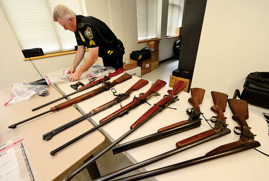 Hour photo / Erik Trautmann Seargent Terry Blake catelogues weapons as The Norwalk Police Department holds a gun buyback program Saturday at Norwalk Police Headquarters wher nearly twenty guns were surrendered for VISA giftcards between $50 and $75 value.