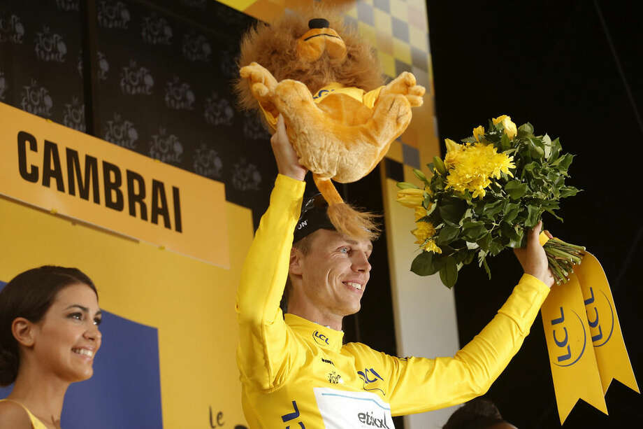 Stage winner Germany's Tony Martin, wearing the overall leader's yellow jersey, celebrates on the podium of the fourth stage of the Tour de France cycling race over 223.5 kilometers (138.9 miles) with start in Seraing, Belgium, and finish in Cambrai, France, Tuesday, July 7, 2015. (AP Photo/Laurent Cipriani)