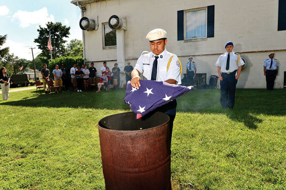 "Hour photo / Erik Trautmann Norwalk High School Airforce ROTC Cadet Master Seargent Victor Sanchez assists in the retirement of american flags in honor of Falg Day during the 8th annual ""A Thank You to All Our Veterans"" Saturday at Frank C. Godfrey Post 12"