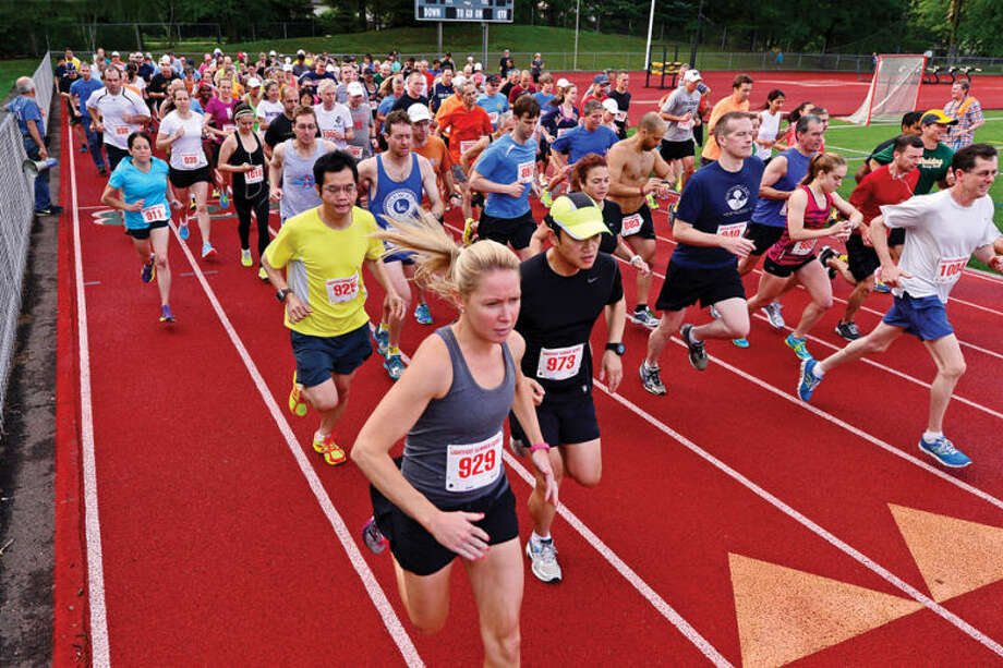 Hour photo / Erik Trautmann Runners start out on the Lightfoot Road Runners Club 3 mile opener at Norwalk High School Saturday.