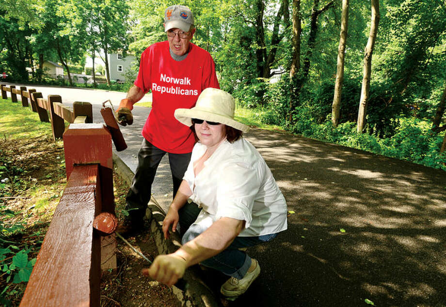 Hour photo / Erik Trautmann Ed Sisson and Emily Wilson join the Norwalk Republicans and the Department of Recreation and Parks as they clean up Flax Hill Park Saturday.