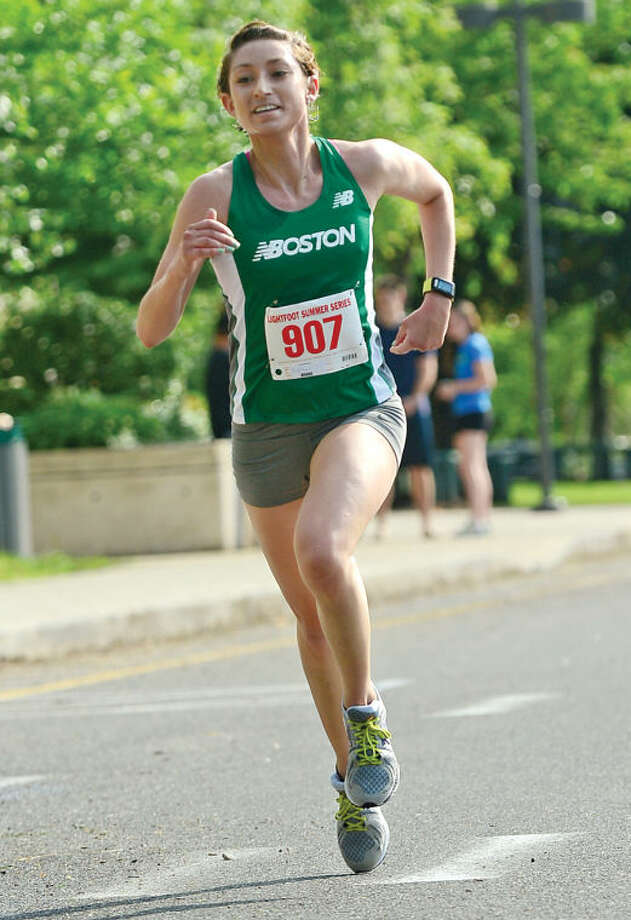 Hour photo / Erik Trautmann Alasia Griebel is the first woman finisher during the Lightfoot Road Runners Club 3 mile opener at Norwalk High School Saturday.