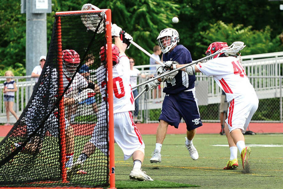 Hour photo / Erik Trautmann Staples # 14 Patrick Lesch shoots on goal as they play Greenwich in the boys Class L lacrosse championship game Saturday at Brien MacMahon High School..