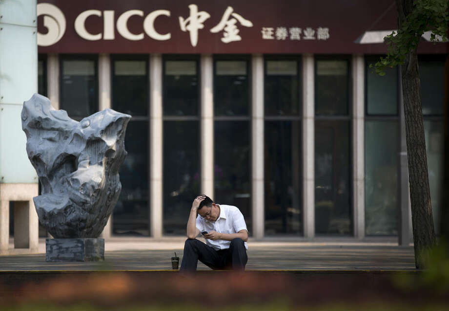 A man rubs his head while browsing his smartphone outside a brokerage house in Beijing Tuesday, July 7, 2015. Chinese stocks fell Tuesday despite official efforts to shore up slumping prices while other Asian markets were mixed after Greece's spiraling crisis weighed on Wall Street. (AP Photo/Andy Wong)