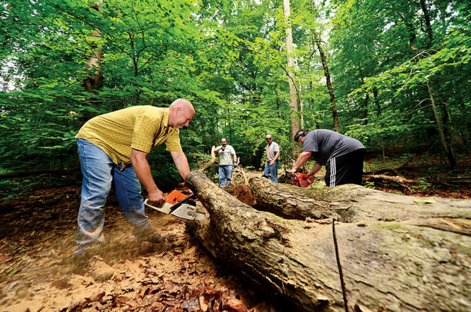 Hour photo / Erik Trautmann Boy Scout Bradley Carrano from Troop 2 directs crews of boy scouts and parents including parent Rob Griffith who work on improving the hiking trails at Oak Hills Park as part of Carrano's Eagle Scout project.