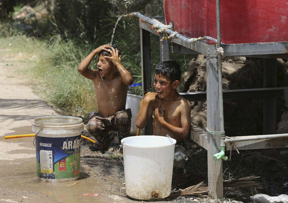 Iraqi displaced children cool themselves with water at a camp for internally displaced people in Baghdad's southern district of Dora on Tuesday, July 7, 2015. The number of people displaced within Iraq due to violence and fighting by the Islamic State group has exceeded 3 million, the United Nations said in June. (AP Photo/Karim Kadim)