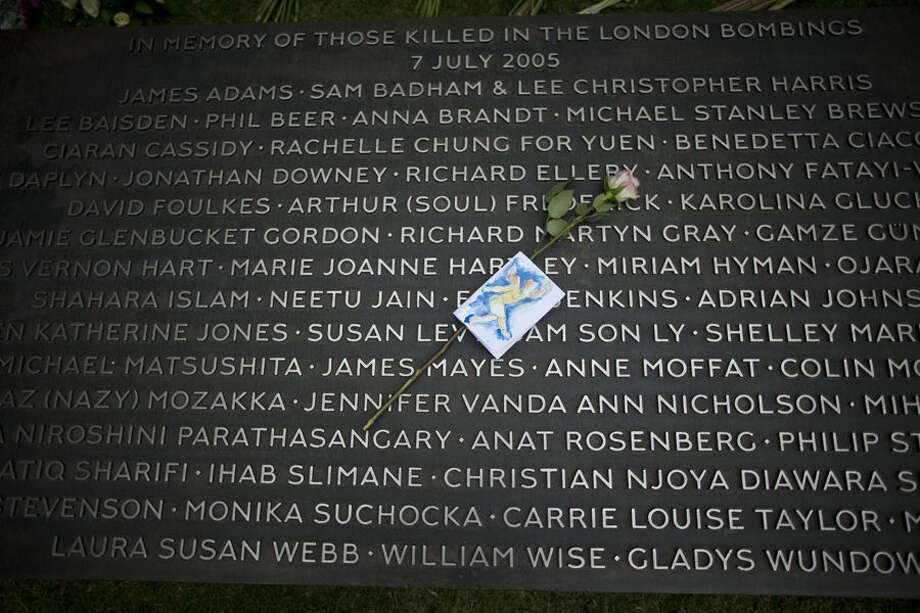 A flower lies on a plaque bearing the names of victims at the 7/7 memorial, on the 10th anniversary of the attacks, in Hyde Park, London, Tuesday, July 7, 2015. Britons marked the 10th anniversary of suicide bomb attacks on London's transit system Tuesday, as Prime Minister David Cameron said the recent slaying of 30 British tourists in Tunisia was a reminder that terror threats remain real and deadly. (AP Photo/Matt Dunham)
