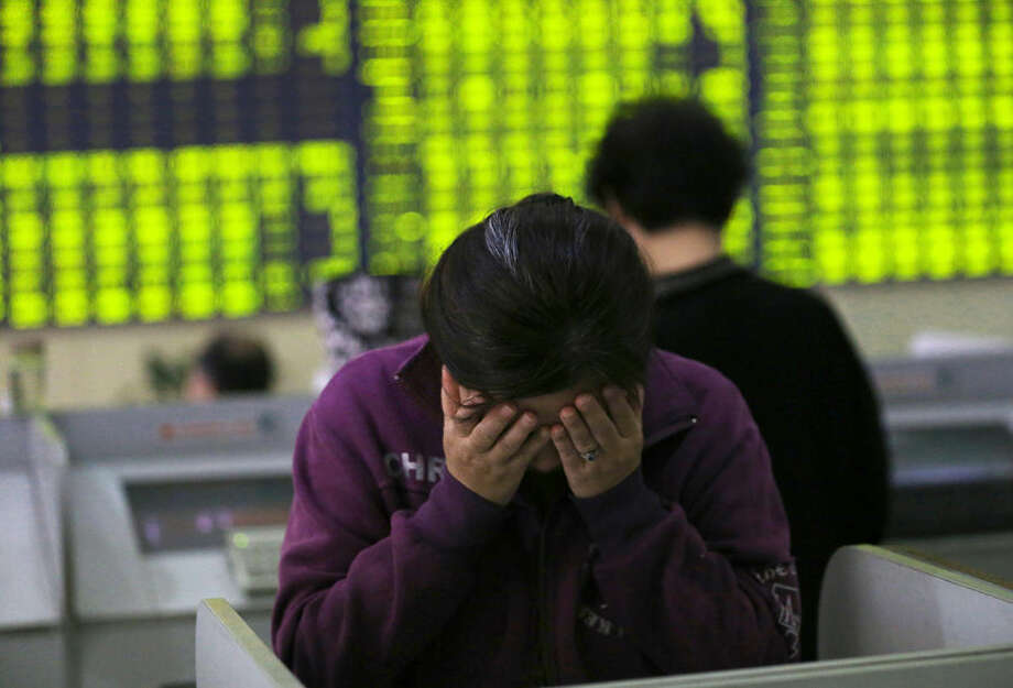 A woman rubs her face as she stands at a computer terminal in a stock brokerage house in Nantong in eastern China's Jiangsu province Wednesday, July 8, 2015. China's Shanghai Composite Index fell 5.9 percent on Wednesday. (Chinatopix via AP) CHINA OUT