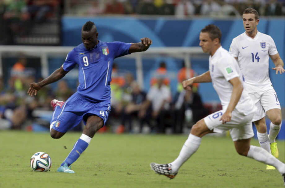 Italy's Mario Balotelli, left, gets in a shot as England's Phil Jagielka, center, and Jordan Henderson, right, defend during the group D World Cup soccer match between England and Italy at the Arena da Amazonia in Manaus, Brazil, Saturday, June 14, 2014. (AP Photo/Martin Mejia)